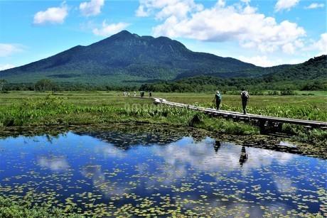 夏の尾瀬ヶ原をハイキングする男女2人と、背後の燧ケ岳と雲を手前の沼にその影を映すの写真素材 [FYI04516496]