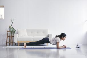 室内でノートパソコンを見ながら運動する女性の写真素材 [FYI04516568]