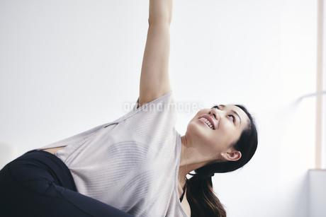 室内でノートパソコンを見ながら運動する女性の写真素材 [FYI04516571]