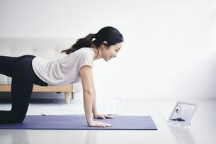 室内でタブレット端末を見ながら運動する女性の写真素材 [FYI04516572]