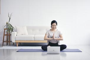 室内でノートパソコンを見ながら運動する女性の写真素材 [FYI04516573]