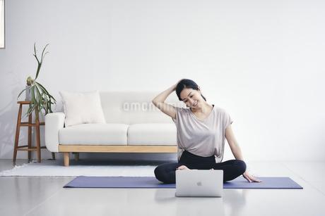 室内でノートパソコンを見ながら運動する女性の写真素材 [FYI04516576]