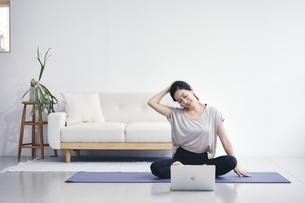 室内でノートパソコンを見ながら運動する女性の写真素材 [FYI04516577]