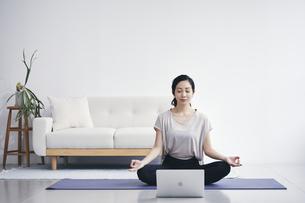 室内でノートパソコンを見ながら運動する女性の写真素材 [FYI04516578]