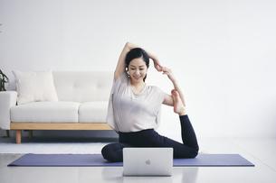室内でノートパソコンを見ながら運動する女性の写真素材 [FYI04516581]