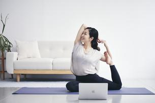 室内でノートパソコンを見ながら運動する女性の写真素材 [FYI04516582]
