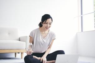 室内でノートパソコンを見ながら運動する女性の写真素材 [FYI04516587]