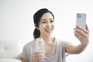 室内でスマートフォンを持ち運動する女性の写真素材 [FYI04516588]