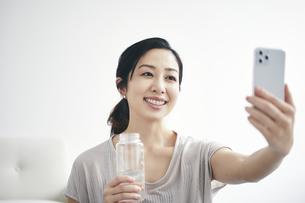 室内でスマートフォンを持ち運動する女性の写真素材 [FYI04516589]