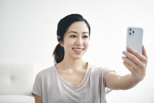 室内でスマートフォンを持ち運動する女性の写真素材 [FYI04516590]