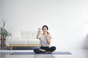 室内でスマートフォンを持ち運動する女性の写真素材 [FYI04516592]