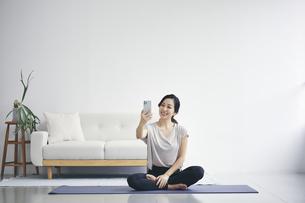 室内でスマートフォンを持ち運動する女性の写真素材 [FYI04516593]