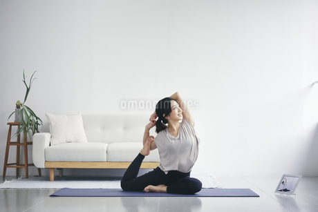 室内でタブレット端末を見ながら運動する女性の写真素材 [FYI04516598]