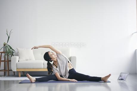 室内でタブレット端末を見ながら運動する女性の写真素材 [FYI04516600]