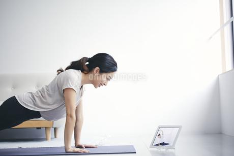 室内でタブレット端末を見ながら運動する女性の写真素材 [FYI04516611]