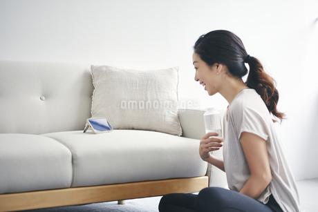 室内でスマートフォンを見ながら運動する女性の写真素材 [FYI04516630]