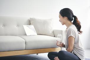 室内でタブレット端末を見ながら運動する女性の写真素材 [FYI04516633]