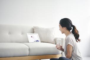 室内でタブレット端末を見ながら運動する女性の写真素材 [FYI04516635]