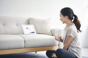 室内でタブレット端末を見ながら運動する女性の写真素材 [FYI04516636]