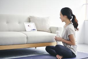 室内でタブレット端末を見ながら運動する女性の写真素材 [FYI04516637]