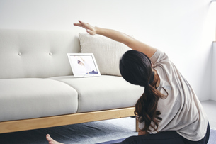 室内でタブレット端末を見ながら運動する女性の写真素材 [FYI04516640]