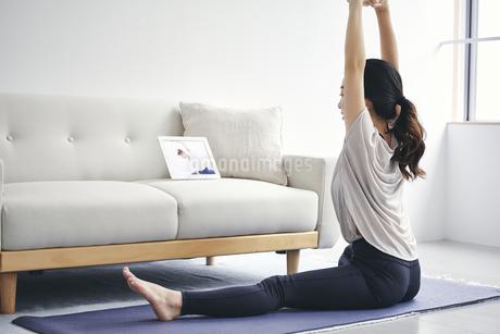 室内でタブレット端末を見ながら運動する女性の写真素材 [FYI04516643]