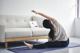 室内でタブレット端末を見ながら運動する女性の写真素材 [FYI04516646]