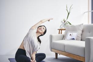 室内でタブレット端末を見ながら運動する女性の写真素材 [FYI04516649]