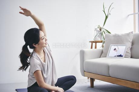室内でタブレット端末を見ながら運動する女性の写真素材 [FYI04516652]
