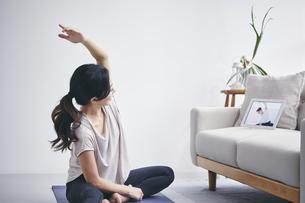 室内でタブレット端末を見ながら運動する女性の写真素材 [FYI04516653]