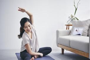 室内でタブレット端末を見ながら運動する女性の写真素材 [FYI04516654]