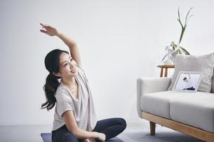室内でタブレット端末を見ながら運動する女性の写真素材 [FYI04516655]