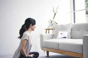 室内でタブレット端末を見ながら運動する女性の写真素材 [FYI04516657]