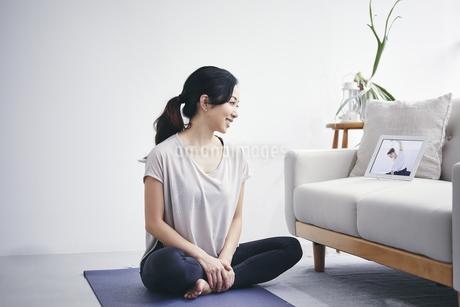室内でタブレット端末を見ながら運動する女性の写真素材 [FYI04516658]