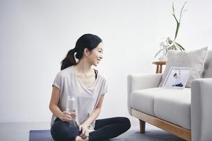 室内でタブレット端末を見ながら運動する女性の写真素材 [FYI04516659]