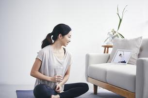 室内でタブレット端末を見ながら運動する女性の写真素材 [FYI04516662]