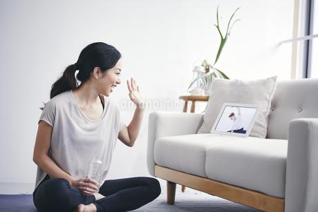 室内でタブレット端末を見ながら運動する女性の写真素材 [FYI04516668]