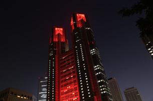 東京アラートの発令に伴い、人々に警戒を呼びかけるために赤くライトアップされた東京都庁の写真素材 [FYI04516757]