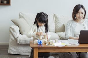 積み木で遊ぶ女の子とテレワークをする母親の写真素材 [FYI04516995]