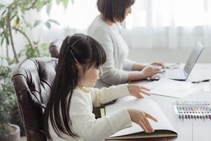 お絵描きをする女の子とテレワークをする母親の写真素材 [FYI04516996]