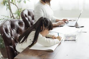 お絵描きをする女の子とテレワークをする母親の写真素材 [FYI04516997]