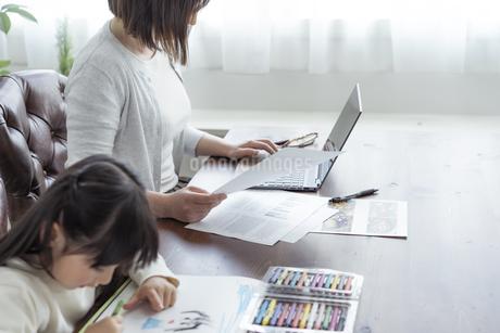 お絵描きをする女の子とテレワークをする母親の写真素材 [FYI04516998]