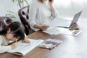 お絵描きをする女の子とテレワークをする母親の写真素材 [FYI04516999]