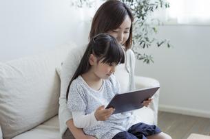 タブレットPCを見る親子の写真素材 [FYI04517000]