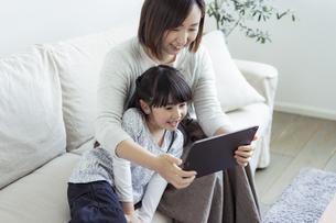 タブレットPCを見る親子の写真素材 [FYI04517003]