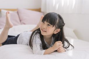 ベッドの上でくつろぐ女の子の写真素材 [FYI04517004]