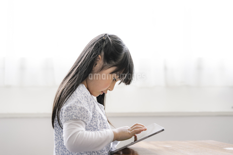 タブレットPCを見る女の子の写真素材 [FYI04517007]