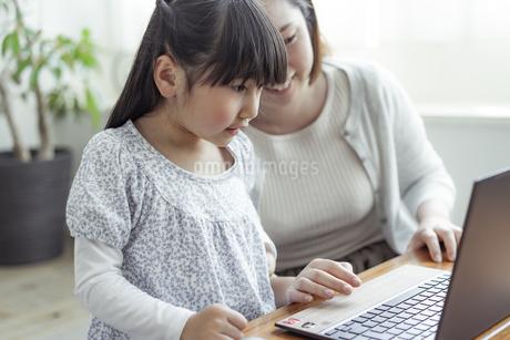ノートパソコンを見る親子の写真素材 [FYI04517009]