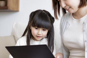 ノートパソコンを見る親子の写真素材 [FYI04517033]