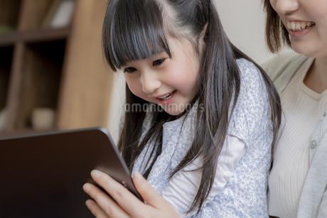 タブレットPCを見る親子の写真素材 [FYI04517055]